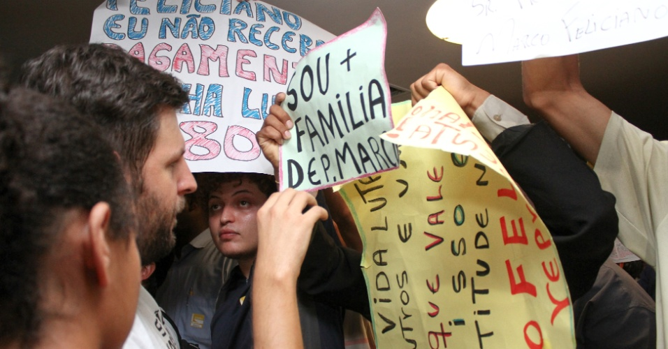 """3.abr.2013 - Manifestantes favoráveis e contrários à permanência do deputado Marco Feliciano (PSC-SP) na presidência da CDH (Comissão de Direitos Humanos e Minorias) da Câmara, protestam do lado de fora da sessão da comissão, nesta quarta-feira (3). Após uma série de protestos anti-Feliciano nas últimas sessões, a CDH aprovou nesta quarta-feira um requerimento para fazer todas as reuniões a portas fechadas, como forma de """"garantir a ordem"""". Só será permitida a entrada de deputados, assessores e jornalistas"""
