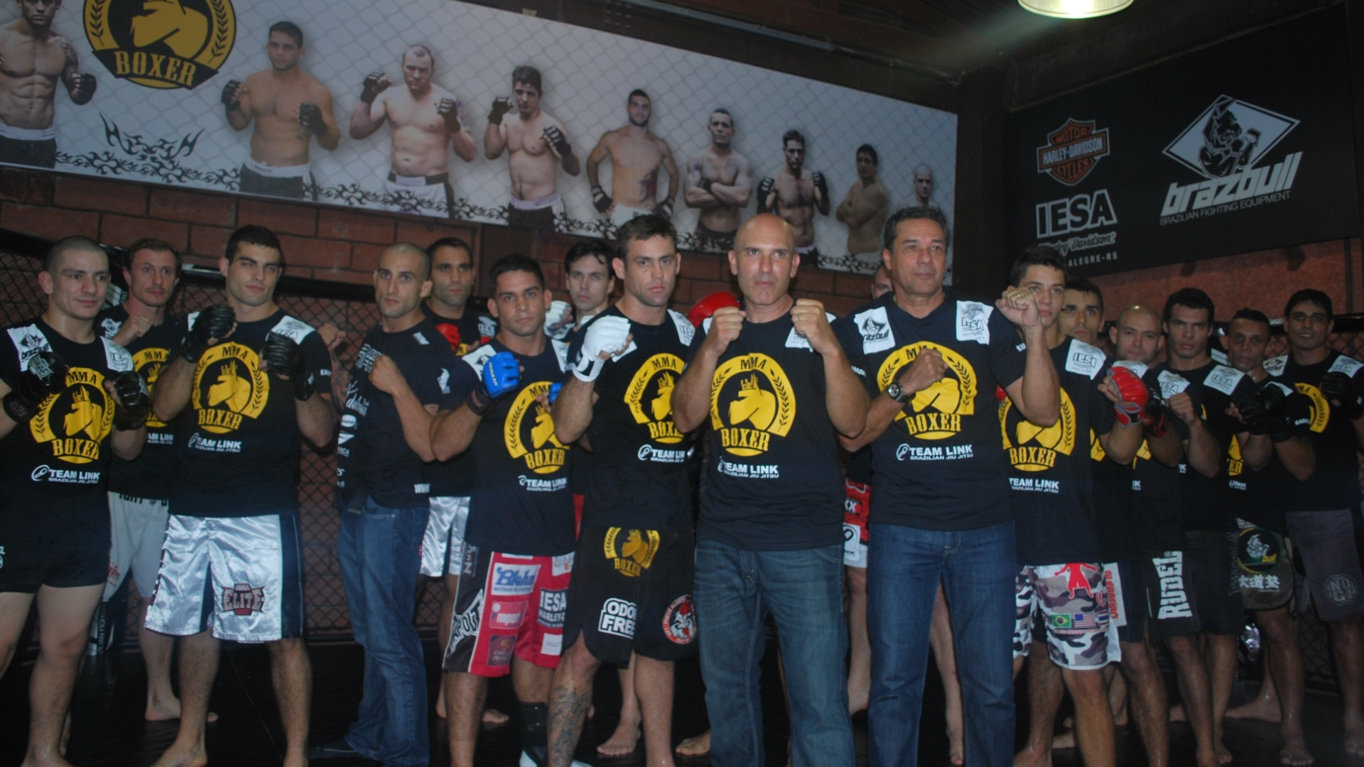 04.04.2012 - Luxa posa ao lado de lutadores de MMA em CT em Porto Alegre
