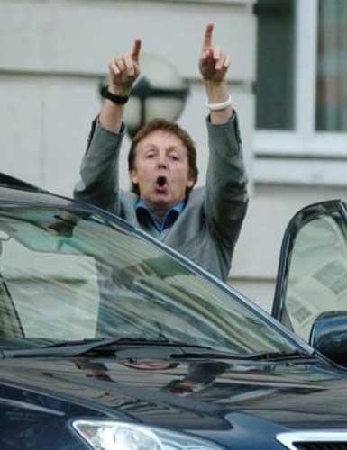 22.abr.2007: Sir Paul McCartney, que está com a pulseira branca simbolizando paz e amor, xinga os fotógrafos que o perseguem nas ruas de Londres