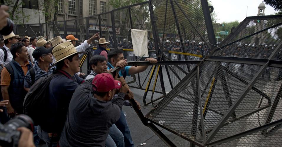 4.abr.2013 - Professores derrubam uma cerca metálica que protegia o Ministério do Interior mexicano, na Cidade do México, durante protesto nesta quinta-feira (4) contra a reforma no sistema educacional proposta pelo governo. Houve confronto com a polícia