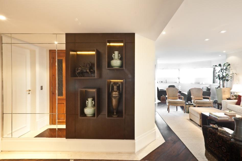 Para dar um maior destaque à entrada do apartamento, a arquiteta Andréa Parreira instalou na parede em frente à porta, uma composição de espelhos com um móvel feito sob medida para colocação de vasos e esculturas