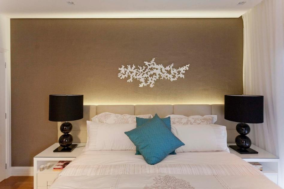 No quarto do casal, a arquiteta Mayra Lopes escolheu um papel de parede (Wallpaper) em uma tonalidade que  combina com os tons de madeira e laca presentes no ambiente. No centro está a peça da Arte Aplicada, desenvolvida pelo artista plástico Cássio, em aço e pintura automotiva, com cortes que lembram rendas