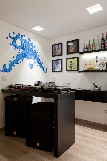 Para o apartamento de um advogado que tem como hobby ser DJ, as arquitetas Andrea Lucchesi e Carolina Razuk optaram pelo grafite do artista Zezão em uma das paredes e na outra, posicionaram quadros e a estante para bebidas. A iluminação focada destaca as decorações