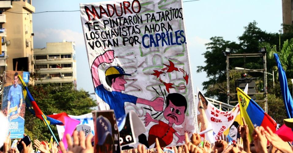 """5.abr.2013 - Cartaz de eleitores afirma que Nicolás Maduro está """"vendo passarinhos"""" e que os chavistas agora votam no candidato da oposição, Henrique Capriles. A faixa foi exibida em evento de campanha realizado na cidade de Porto Ordaz, no nordeste Venezuelano. O oposicionista, assim como seu adversário nas eleições do próximo dia 14, o presidente interino Nicolás Maduro, buscaram o apoio de artistas do país nesta sexta-feira (5)"""