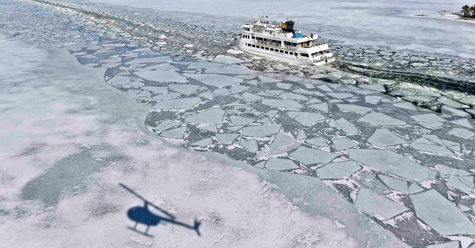 """5.abr.2013 - Um helicóptero projeta sombra sobre o gelo próximo de onde passa o navio de passeio """"Soderarm"""", em um canal feito por um navio quebra-gelo à ilha de Husaro no arquipélago de Estocolmo, na Suécia, nesta sexta-feira (5). Segundo o Instituto Meteorológico e Hidrológico da Suécia (SMHI, em inglês), a cobertura de gelo no mar Báltico é a mais volumosa e mais extensa já registrada"""