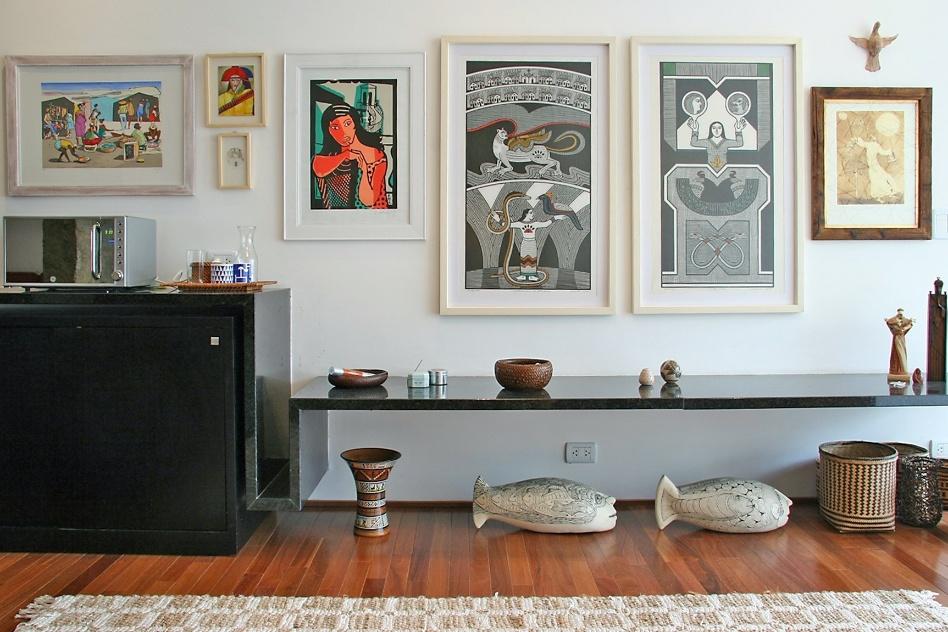 """No projeto do apartamento, assinado por FGMF Arquitetos, a propoNo projeto do apartamento, assinado pelo escritório FGMF Arquitetos, a proposta é preencher a extensão da parede com quadros que """"dialogam"""" com os objetos de arte étnicos dispostos no ambientesta é preencher a extensão da parede com quadros que """"dialogam"""" com os objetos de arte étnicos dispostos no ambiente"""