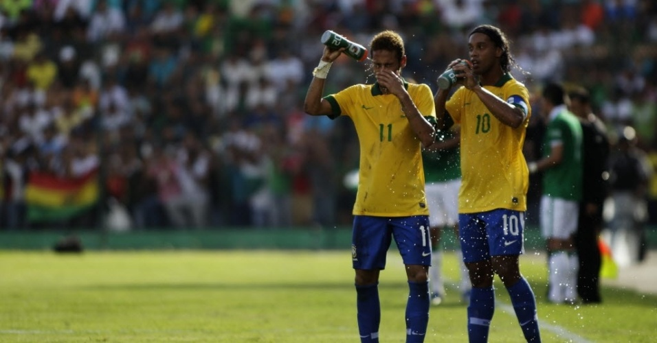 06.abr.2013 - Dupla Neymar e Ronaldinho Gacho se refresca durante o amistoso entre Brasil e Bolvia
