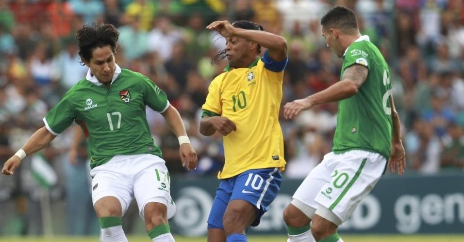 06.abr.2013 - Ronaldinho Gaúcho tenta se desvencilhar de dois marcadores bolivianos em amistoso da seleção brasileira