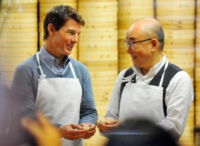 6.abril.2013 - Tom Cruise visita restaurante em Taiwan e aprende a fazer um bolinho típico