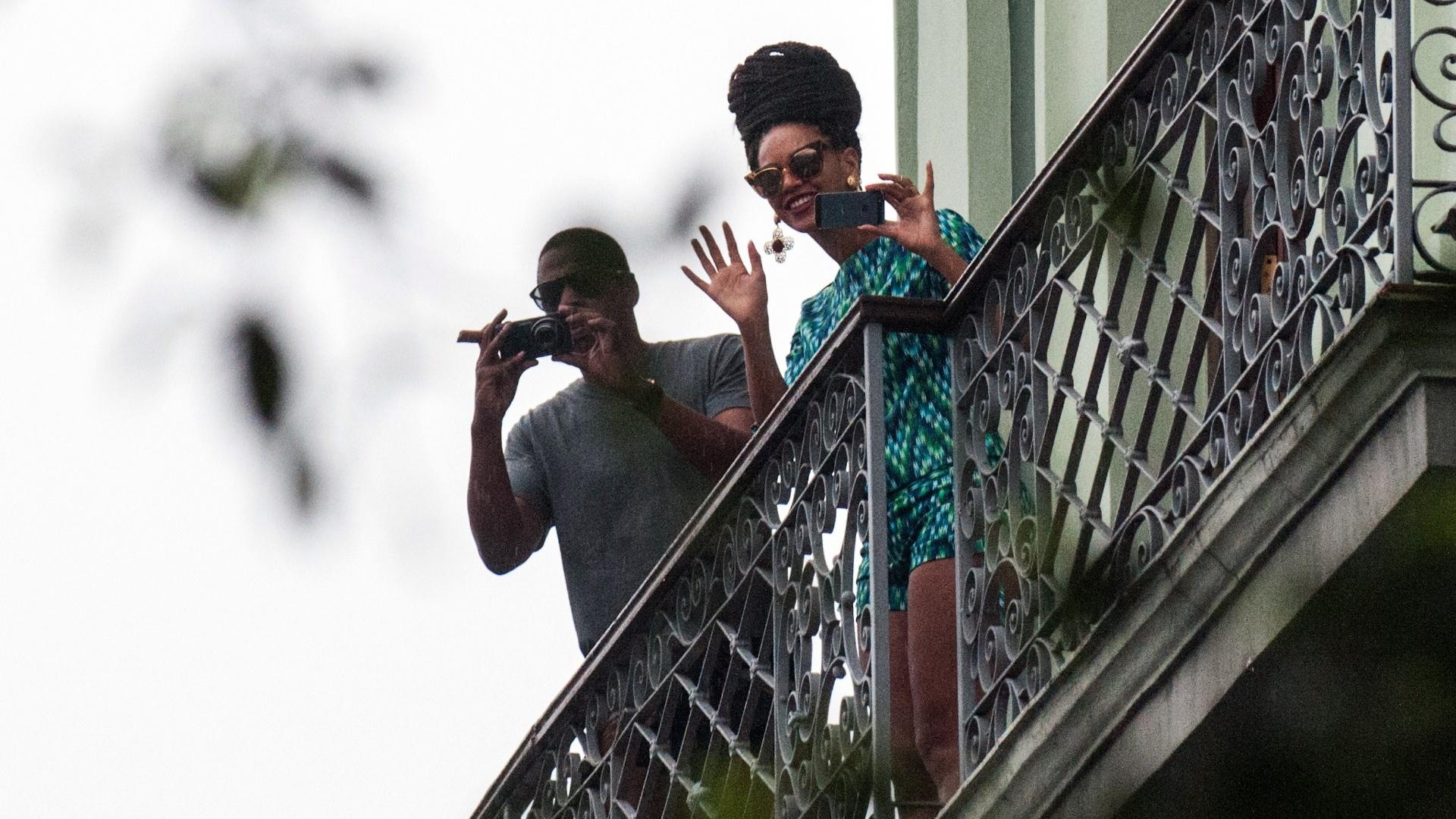 5.abril.2013 - Jay-Z e Beyonce acenam para fãs e fotografam a movimentação em frente ao hotel Saratoga, em Havana