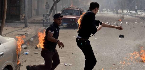 Cristãos coptas egípcios tentam apagar fogo de suas roupas depois de terem sido atacados por indivíduos não identificados fora da catedral, no bairro central de Abbassiya, no Cairo