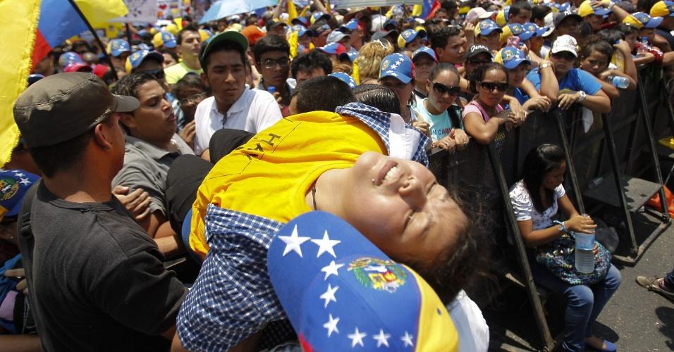 7.abr.2013 - Mulher desmaia durante passeata em apoio ao candidato da oposição nas eleições presidenciais venezuelanas, Henrique Capriles, em Caracas, neste domingo (7)