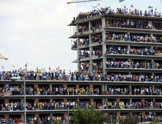 7.abr.2013 - Pessoas acompanham de prédio em construção comício de campanha do candidato da oposição à presidência da Venezuela Henrique Capriles em Caracas neste domingo (7). As eleições presidenciais venezuelanas ocorrem no dia 14 de abril