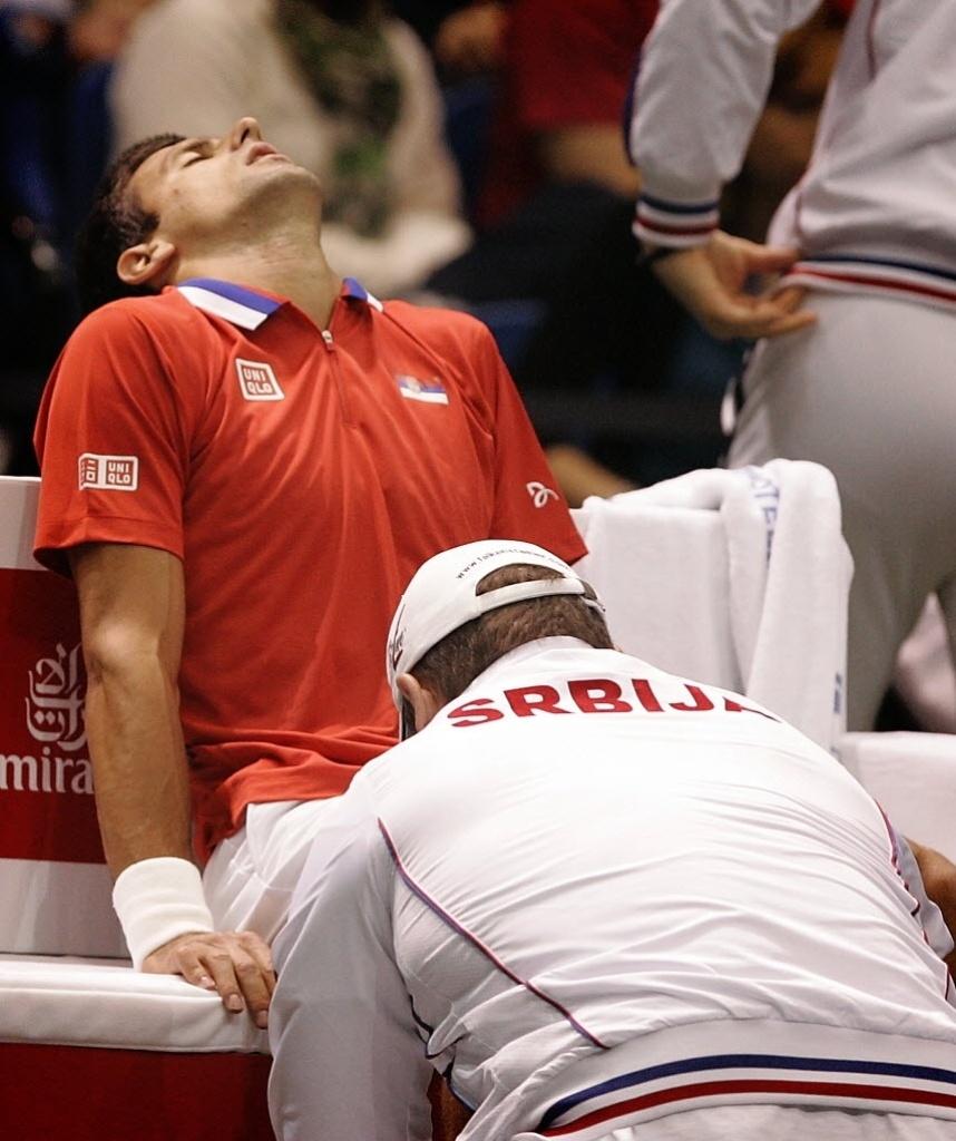 07.abr.2013 - Djokovic é atendido pelo médico após sofrer uma torção no tornozelo em jogo das quartas da Copa Davis contra o norte-americano Sam Querrey