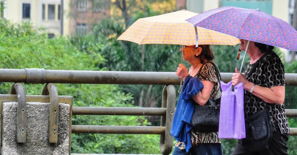 8.abr.2013 - Moradores de São Paulo (SP) se protegem da chuva no Viaduto do Chá, região central da cidade, na manhã desta segunda-feira