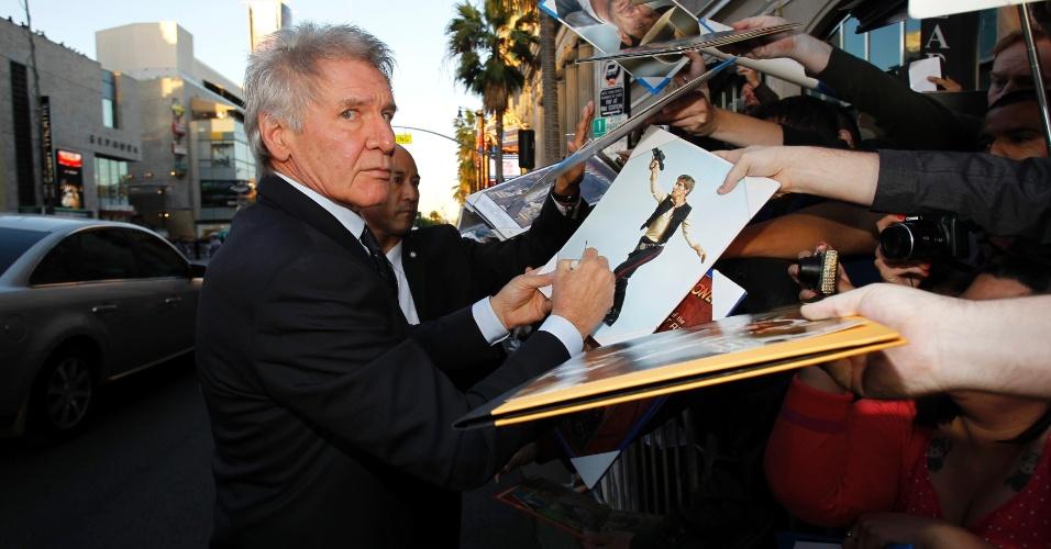 """10.abr.2013 - Harrison Ford autografa diversos pôsteres de seus antigos personagens, como Indiana Jones, durante a pré-estreia do filme """"42"""", em Los Angeles"""