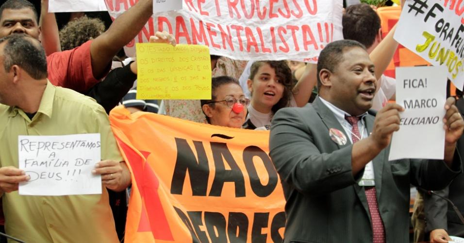 10.abr.2013 - Manifestantes a favor e contrários à permanência do deputado Marco Feliciano (PSC-SP) na presidência da Comissão de Direitos Humanos da Câmara protestam durante sessão da comissão, nesta quarta-feira (10). Após os protestos, Feliciano transferiu a sessão para uma outra sala e proibiu o acesso dos manifestantes