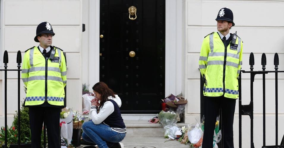 10.abr.2013 - Mulher reza após colocar flores na porta da residência da ex-primeira-ministra britânica Margaret Thatcher, no centro de Londres, no reino Unido, nesta quarta-feira (10). Thatcher dominou a política britânica por duas décadas e morreu na segunda-feira (8), após um derrame