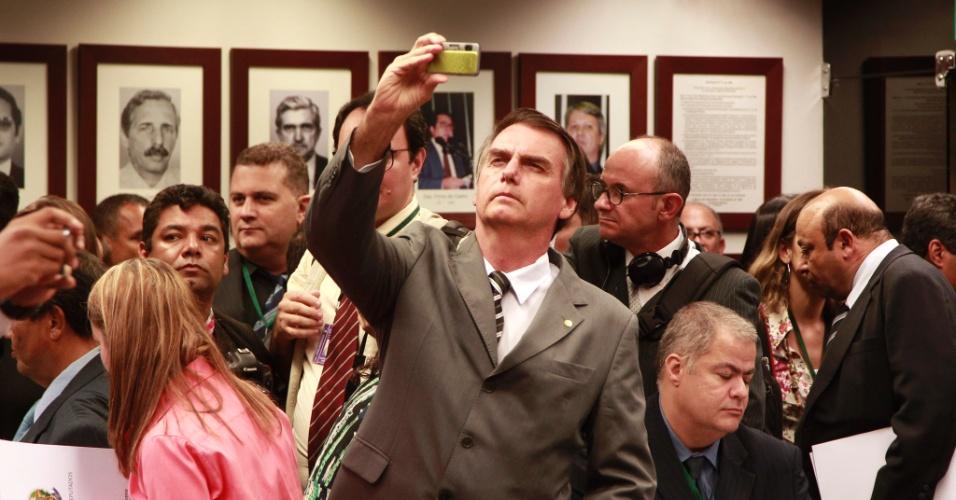 10.abr.2013 - O deputado Jair Bolsonaro (PP-RJ) fotografa manifestantes que protestavam na sessão da Comissão de Direitos Humanos da Câmara desta quarta-feira (10). A sessão foi interrompida e transferida a uma outra sala, sem a presença dos manifestantes, por causa dos protestos contrários e a favor da permanência do deputado Marco Feliciano (PSC-SP) na presidência da comissão