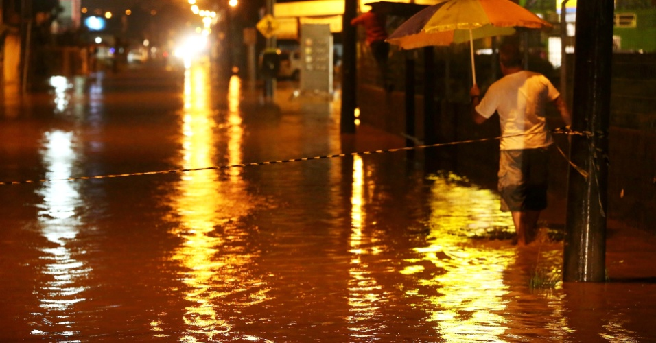 9.abr.2013 - Homem se esforça para caminhar em meio à inundação em Palhoça, na Grande Florianópolis, na noite desta terça-feira (9). A forte chuva que atingiu a cidade provocou alagamentos nos bairros Passa Vinte e Ponte do Imaruim. O corpo de bombeiros da cidade está nos locais mais atingidos e ainda avalia os estragos