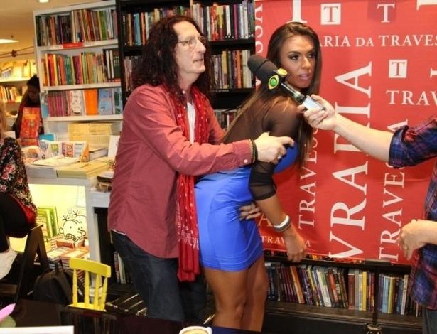 10.abr.2013 - Diretor teatral Gerald Thomas agarra Nicole Bahls durante lançamento de novo livro. Nicole, que já foi panicat, retornou ao