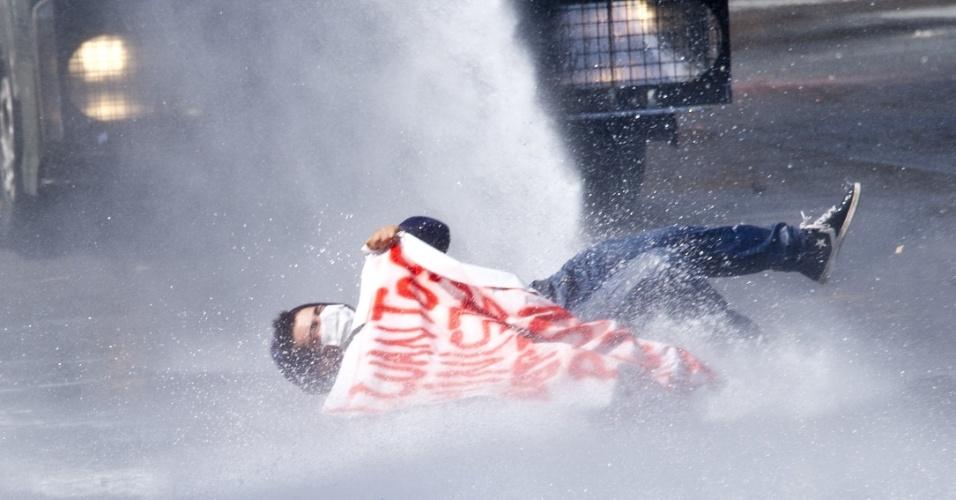 11.abr.2013 - Estudante é atingido por jato de água durante manifestação que reuniu milhares de chilenos nesta quinta-feira (11). A marcha percorreu as ruas de Santiago para exigir uma educação pública gratuita e de melhor qualidade