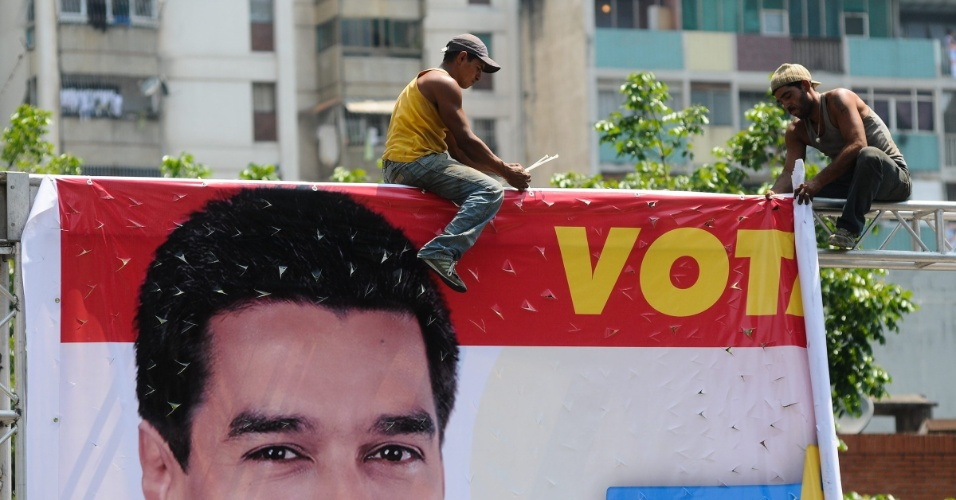 11.abr.2013 - Homens retiram propaganda eleitoral do candidato governista à presidência Nicolás Maduro, no último dia de campanha. No próximo domingo (14) será eleito o primeiro presidente eleito da era pós-Hugo Chávez