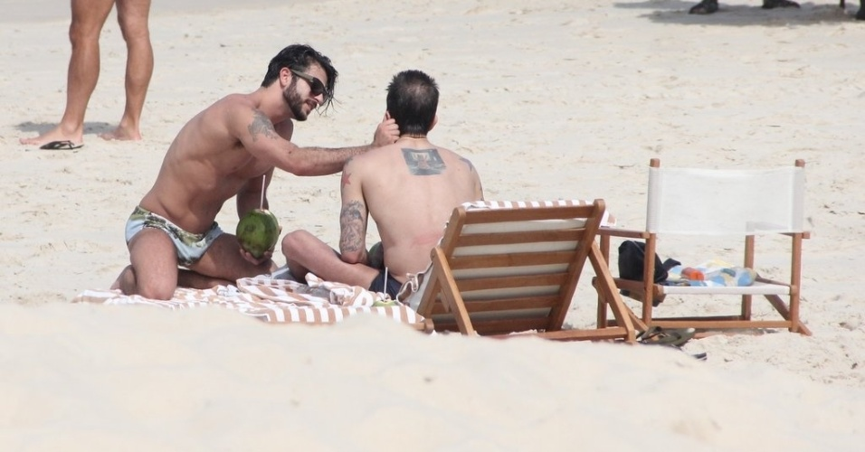 11.abr.2013 - O brasileiro Harry Louis acaricia o namorado, o estilista Marc Jacobs, na praia de Ipanema, na zona sul do Rio