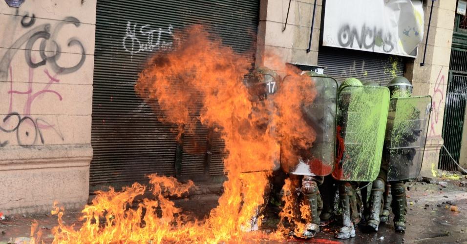 11.abr.2013 - Policiais se protegem durante manifestação que reuniu milhares de chilenos nesta quinta-feira (11). A marcha percorreu as ruas de Santiago para exigir uma educação pública gratuita e de melhor qualidade
