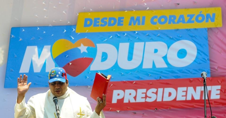 11.abr.2013 - Sacerdote reza perto de uma propaganda eleitoral do candidato governista à presidência Nicolás Maduro. No próximo domingo (14) será eleito o primeiro presidente eleito da era pós-Hugo Chávez