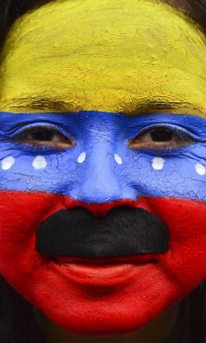 11.abr.2013 - Eleitora de Nicolás Maduro pinta o rosto com bigode do candidato e com as cores da bandeira da Venezuela durante comício do último dia de campanha em Caracas, na Venezuela. No próximo domingo (14) será eleito o primeiro presidente eleito da era pós-Hugo Chávez