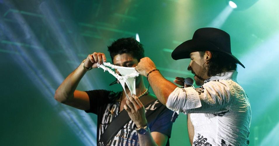 11.abr.2013 - Munhoz e Mariano brincam com calcinha jogada no palco durante show no Villa Country, em São Paulo