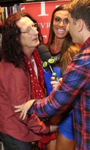 11.abr.2013 - O diretor teatral Gerald Thomas tenta enfiar a mão sob o vestido da ex-panicat Nicole Bahls durante lançamento de livro