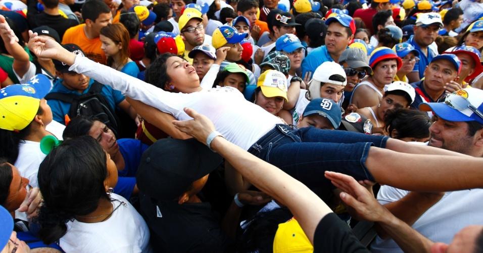 12.abr.2013 - Apoiadora do candidato da oposição à Presidência da Venezuela, Henrique Capriles, é socorrida por populares após passar mal e desmaiar durante um comício de campanha, no Estado de Lara