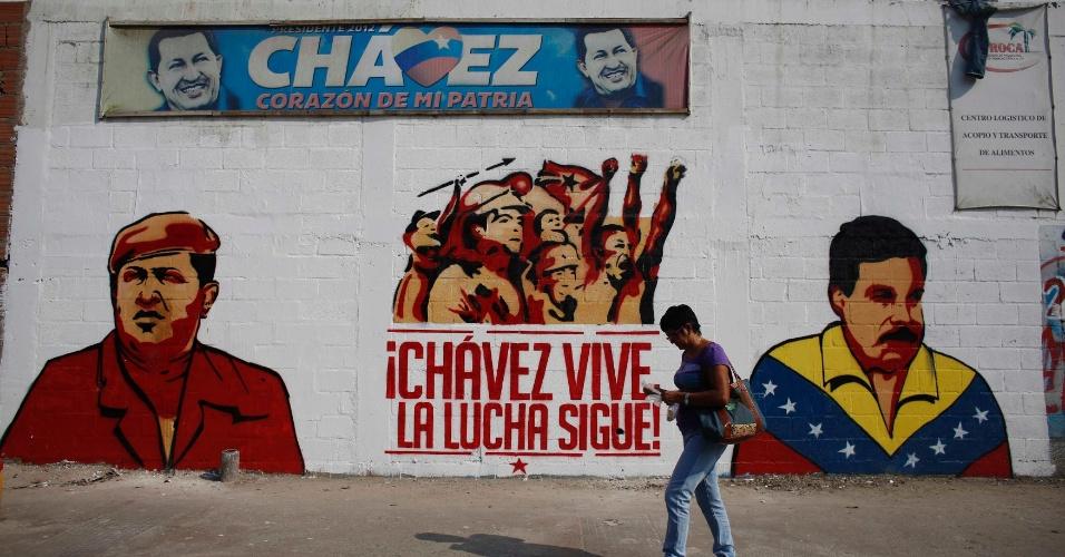 """12.abr.2013 - Pedestre caminha próximo a muro com desenho do candidato governista à presidência da Venezuela e presidente em exercício Nicolás Maduro, ao lado de seu antecessor, Hugo Chávez e com a frase """"Chávez vive, a luta segue"""". No próximo domingo (14) será eleito o primeiro presidente eleito da era pós-Hugo Chávez"""