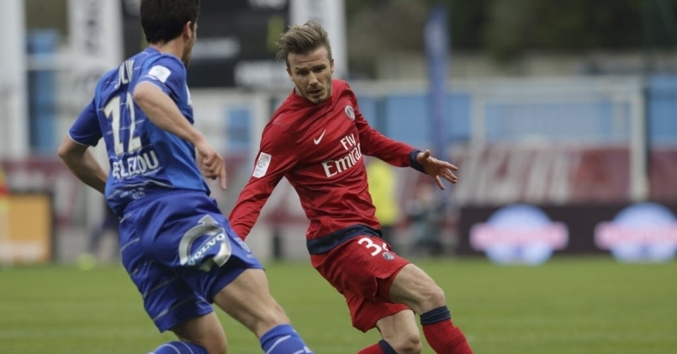 13.abr.2013 - David Beckham (dir.), meia do PSG, disputa a bola com Maxime Colin, do Troyes, em partida do Campeonato Francês
