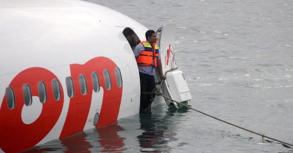 13.abr.2013 - Funcionário de equipe de resgate trabalha em avião que caiu no mar após pouso mal-sucedido no aeroporto internacional de Bali, na Indonésia. Os passageiros sobreviveram