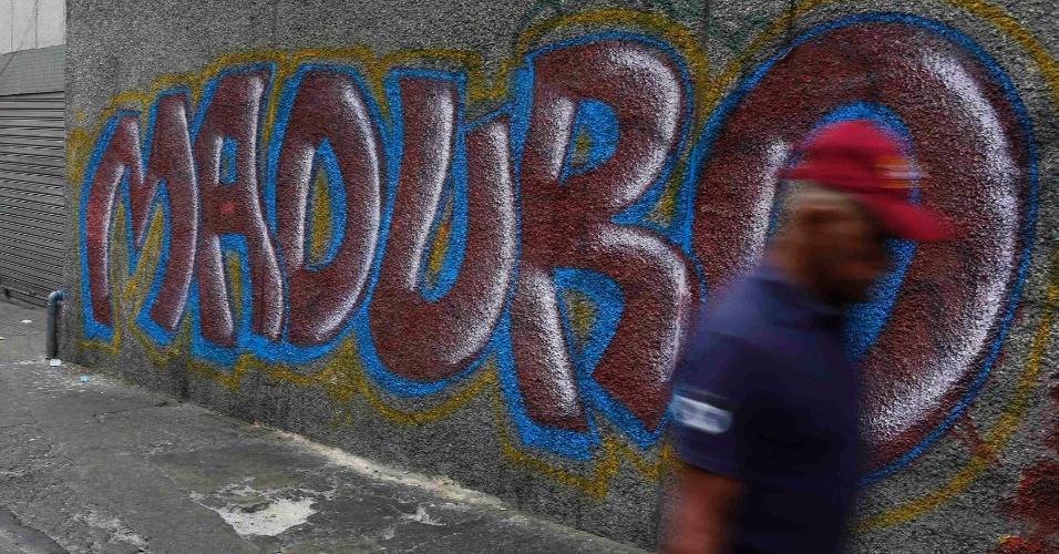 13.abr.2013 - Homem passa em frente a um grafite com o sobrenome de Nicolas Maduro, candidato à presidência da Venezuela. O povo do país sul-americano deverá escolher entre Maduro, candidato da situação, e Henrique Capriles, da oposição