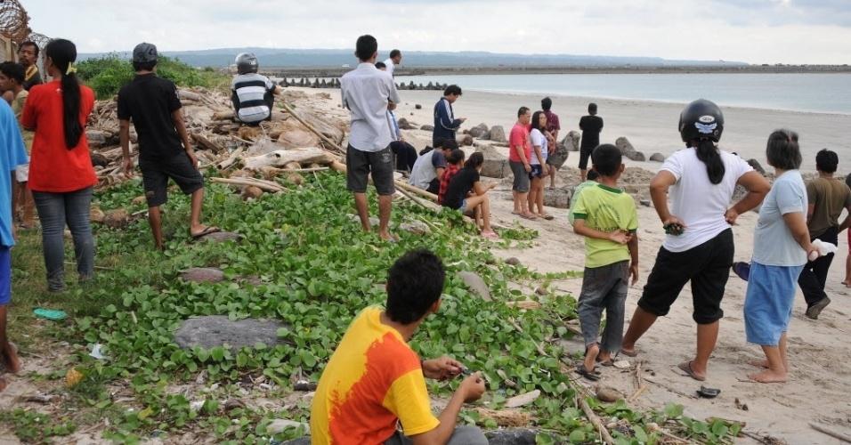 13.abr.2013 - Moradores observam da praia o avião caído no mar, ao lado do aeroporto internacional de Bali, na Indonésia. Os passageiros sobreviveram