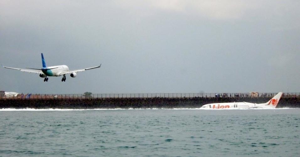 13.abr.2013 - Movimento de aviões (ao fundo) no aeroporto internacional da Bali, na Indonésia, perto de onde um avião caiu no mar neste sábado (13). Os passageiros sobreviveram