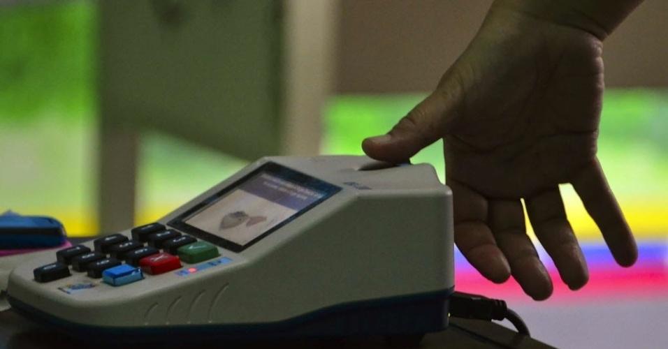 14.abr.2013 - Homem marca digitais em seção eleitoral de Caracas neste domingo (14), dia de eleição presidencial no país