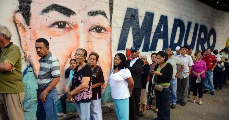 14.abr.2013 - Pessoas fazem fila para votar em Caracas em frente a um muro com propaganda de Nicolás Maduro, candidato que era apoiado pelo ex-presidente Hugo Chávez. Em pesquisas de opinião realizadas na Venezuela, Maduro aparece com vantagem sobre Henrique Capriles, candidato da oposição