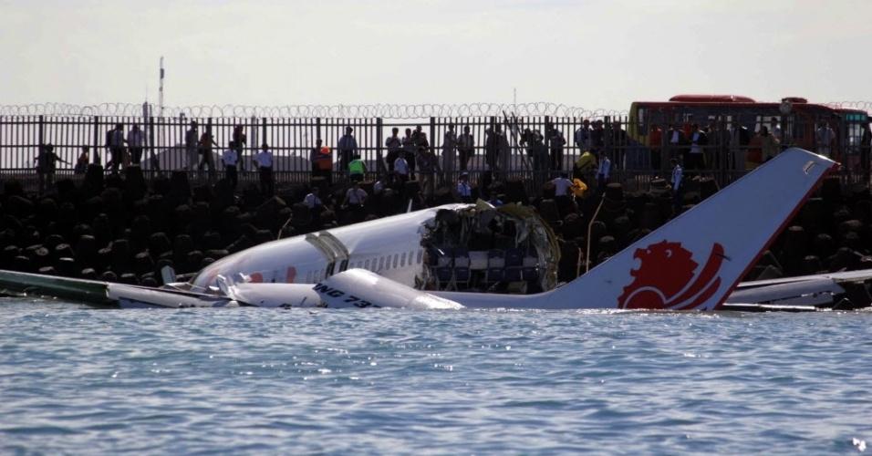 14.abr.2013 - Público (ao fundo) observa destroços de avião que caiu no mar em área ao lado do aeroporto internacional da ilha de Bali, na Indonésia