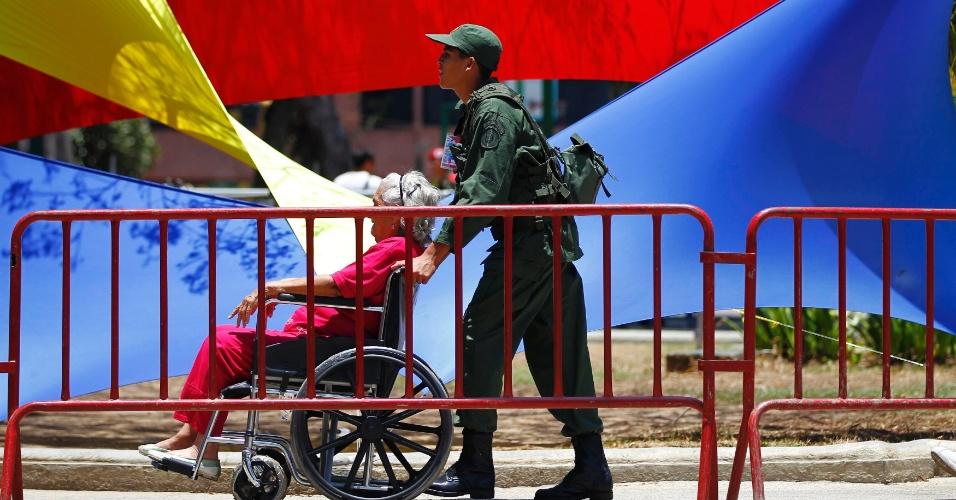 14.abr.2013 - Soldado leva homem de cadeira de rodas até zona eleitoral para votar durante o pleito que vai decidir o próximo presidente da Venezuela. A disputa está polarizada entre Nicolás Maduro, presidente interino do país, e Henrique Capriles, candidato da oposição
