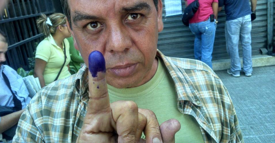 14.abr.2013 0 Raul Aguilera, 49,mostra dedo sujo de tinta após votar no colégio La Consolação, no bairro de Las Palmas, em Caracas
