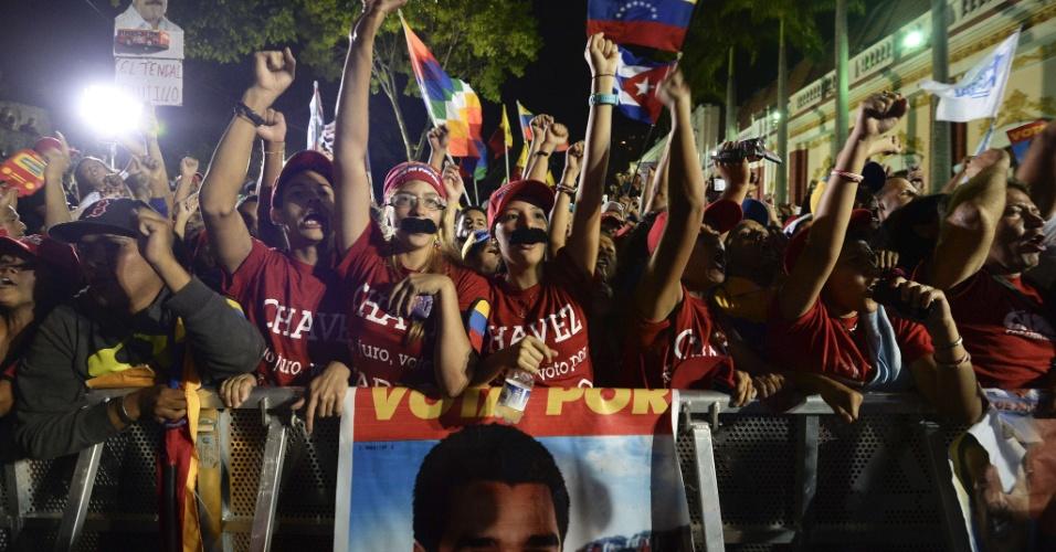 15.abr.2013 - Eleitores de Nicolás Maduro, novo presidente da Venezuela, mostram seus bigodes falsos, inspirados no adereço facial usado pelo político chavista, comemoram o resultado da eleição nas ruas da capital Caracas