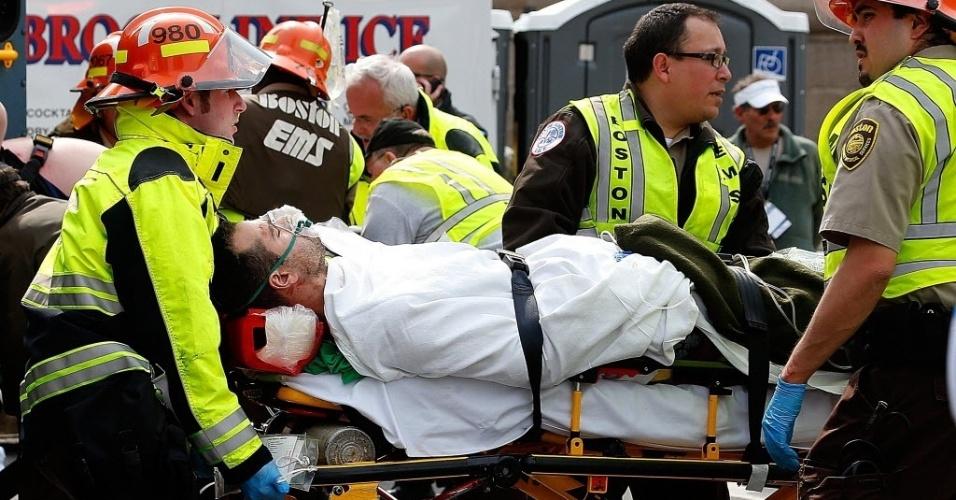 15.abr.2013 - Homem recebe primeiros atendimentos e é levado para ambulância após se ferir em explosões próximas à linha de chegada da Maratona de Boston