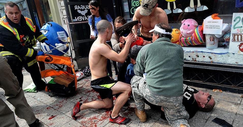 15.abr.2013 - Homens tentam ajudar ferido nos ataques ocorridos durante a Maratona de Boston, no Estados Unidos