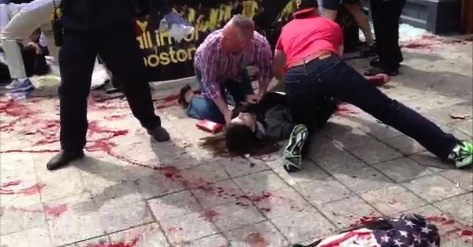 15.abr.2013 - Homens tentam ajudar vítima na calçada, após as explosões que atingiram Boston durante a Maratona da cidade