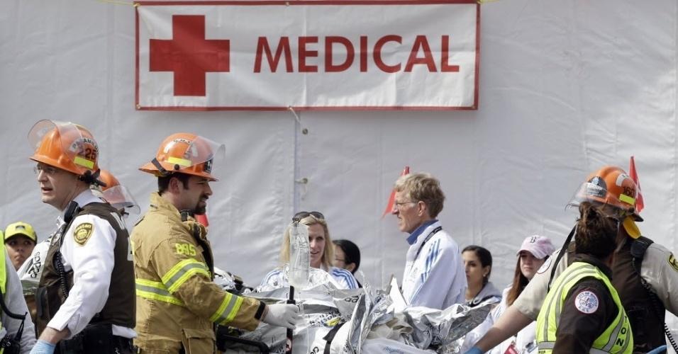 15.abr.2013 - Médicos e bombeiros trabalham no atendimento a feridos após explosões na Maratona de Boston